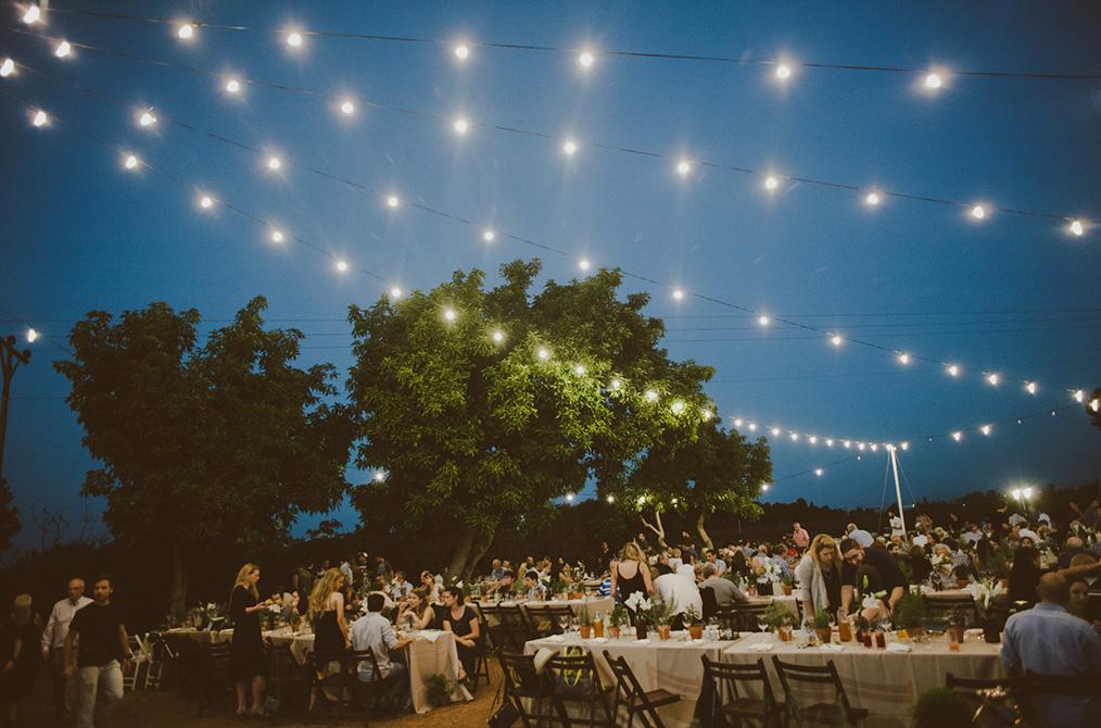 אזור ישיבת האוכל עם גרילנדות מנצנצות בלב השטח. מתוך החתונה של נטע וטל. צילום: חגי גלילי